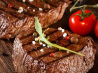 Beef steak on a barbecue grill with flames with vegetables